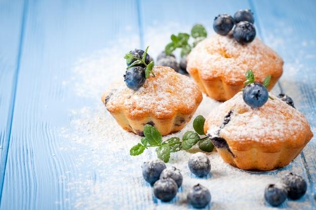 Blaubeermuffin. selbst gemachter gebackener kleiner kuchen mit blaubeeren, frische beeren, minze auf hölzernem hintergrund.
