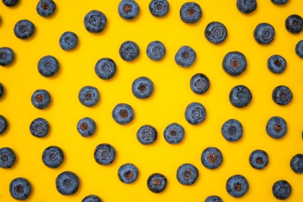 Blaubeermuster auf gelbem hintergrund. reife blaubeeren textur nahaufnahme.
