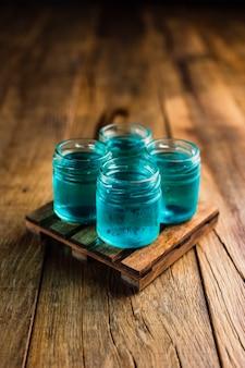 Blaue alkoholische schützen oder schussgetränke auf holztisch