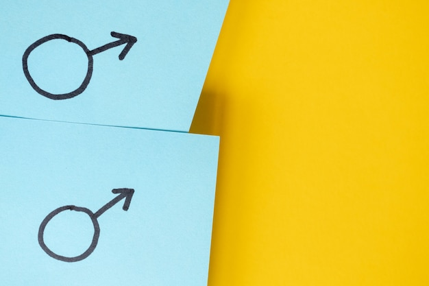 Blaue aufkleber mit geschlechtssymbolen von mars über gelbem hintergrund