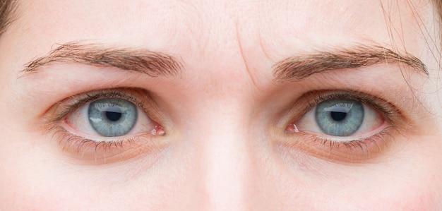 Blaue augen der jungen hübschen frau schließen oben. trauriger ausdruck