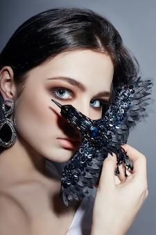 Blaue augen des brunettemädchens, die schwarzen broschenvogel halten