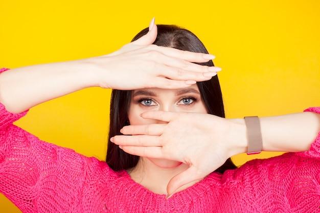 Blaue augen einer frau, beleuchtet von den handflächen, die den oberen teil der stirn und den unteren teil des gesichts bedecken. das konzept von hellen augen, kosmetischem make-up und mascara.