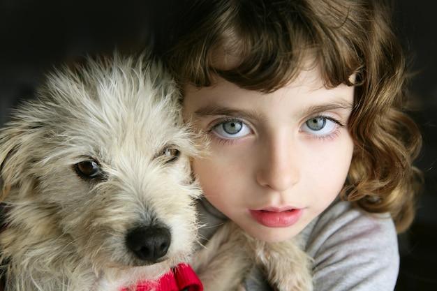 Blaue augen mädchen umarmen ein kleines hundeportrait des haarigen welpen