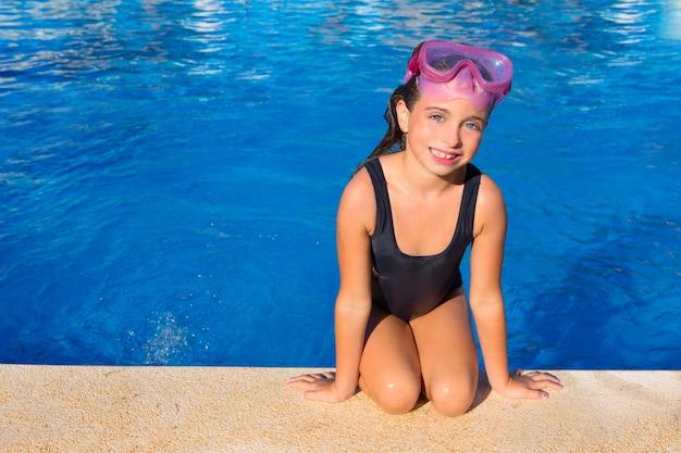 Blaue augen scherzen mädchen auf knien auf blauem pool poolside