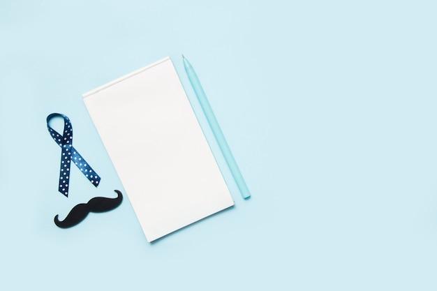Blaue bänder mit dem schnurrbart und notizblock mit stift