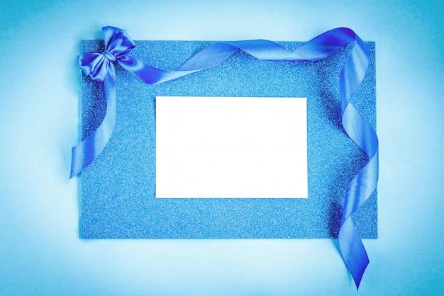 Blaue bandschleife auf blauem glitzerhintergrund. festlicher hintergrund.