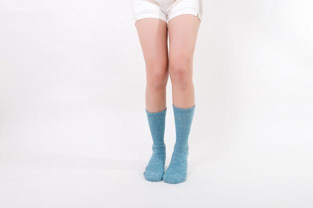 Blaue baumwollsocken an den füßen der schönen frau. isoliert auf weißem hintergrund. studiobeleuchtung