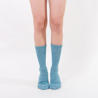 Blaue baumwollsocken an den füßen der schönen frau. isoliert auf weißem hintergrund.