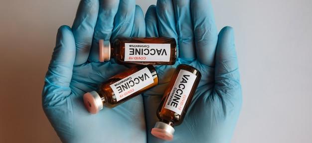 Blaue behandschuhte hände, die glasfläschchen mit coronavirus-covid-19-impfstoff halten, draufsicht. ampullen des covid-impfstoffs hautnah. konzept der massenimmunisierung.