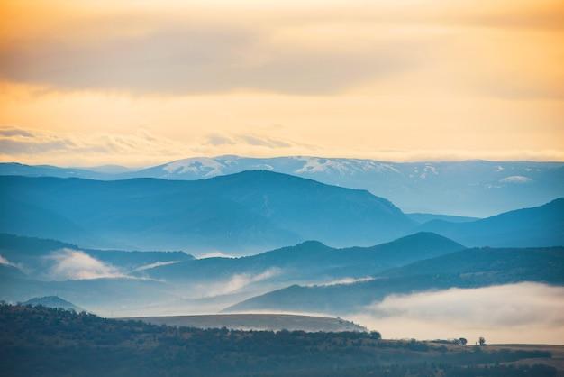 Blaue berge bedeckt mit nebel gegen sonnenuntergang