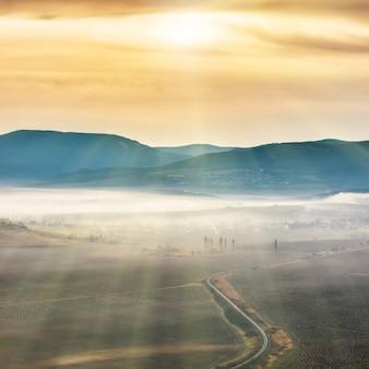 Blaue berge und straße bedeckt mit nebel gegen sonnenuntergang. helle sonne scheint am himmel