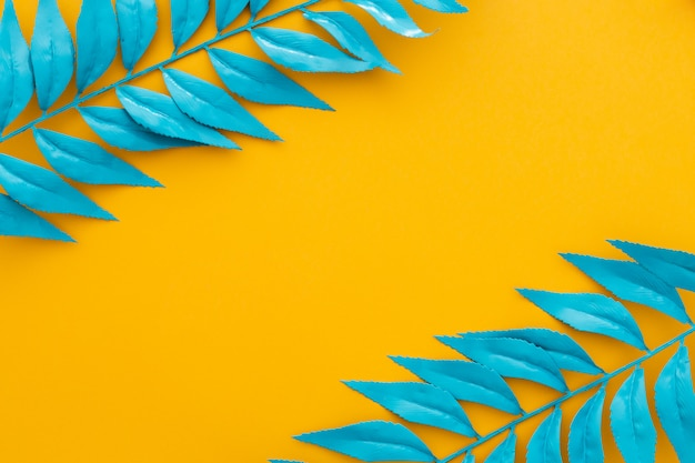 Blaue blätter auf gelbem grund