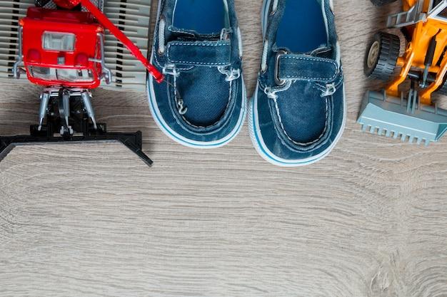 Blaue bootsschuhe für nahen satz des jungen des autos spielen auf grauem hölzernem hintergrund.