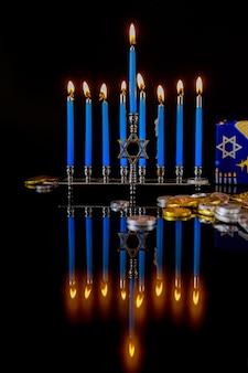 Blaue brennende kerzen auf menora mit schokoladenmünzen für chanukka jüdischen feiertag.