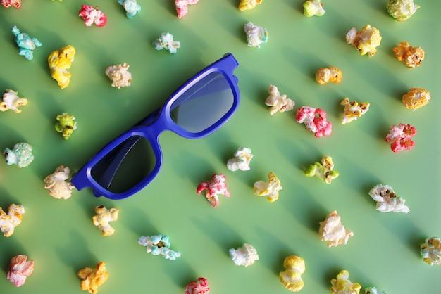 Blaue brille, um den film in 3d zwischen farbigem popcorn zu sehen.
