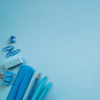 Blaue bürowerkzeuge auf blauer oberfläche