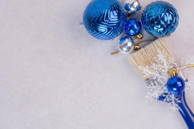 Blaue bürste mit weihnachtskugeln auf weißem tisch.