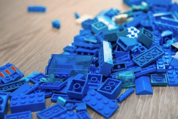 Blaue details des designers der kinder auf hölzernem hintergrund. gebäude, spiele, kindheit, schöpfer-thema