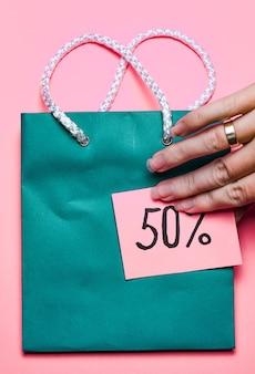 Blaue einkaufstasche mit einem aufkleber, der 50% rabatt und frauenhand auf einer hellrosa oberfläche sagt