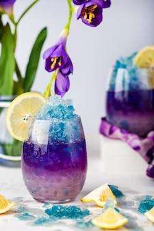 Blaue eislimonade der schmetterlingserbsenblume mit zitronen- und kokosnusssirup