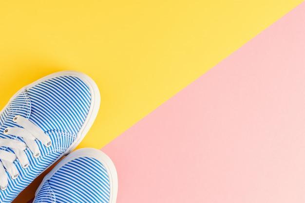 Blaue entfernte turnschuhe auf draufsichtebene des gelben und rosa pastellhintergrundes