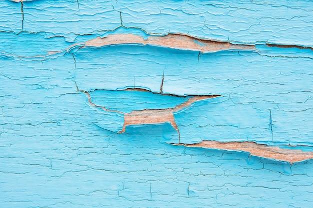 Blaue farbe an einer wand knacken und abblättern. weinleseholzhintergrund mit abblätternder farbe. altes brett mit bestrahlter farbe