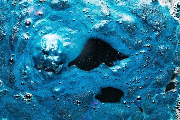 Blaue farbe, die auf schmutziges wasser ausbreitet