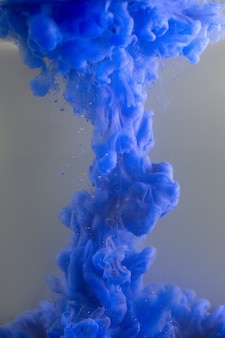 Blaue farbe, die in wasser gießt.