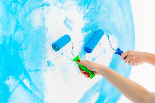 Blaue farbmalereiwand mit rolle in der hand.