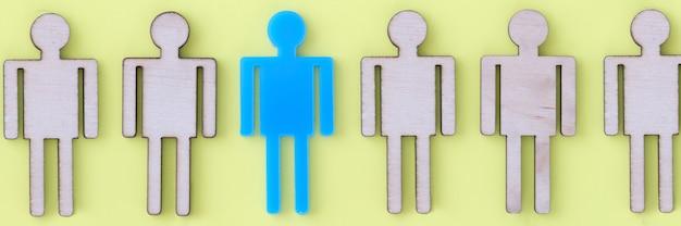 Blaue figur des mannes, der unter holz auf gelbem hintergrund nahaufnahme liegt