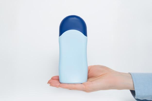 Blaue flasche für kosmetisches produkt in einer weiblichen hand.
