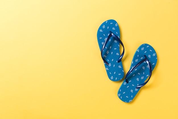 Blaue flip-flops auf gelbem hintergrund. draufsicht mit kopienraum.