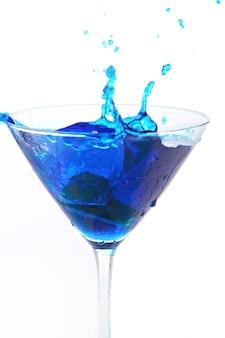 Blaue flüssigkeit, die in glas gießt