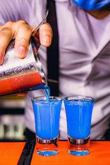 Blaue flüssigkeit im wodka-schnapsglas an der bartheke im nachtclub.