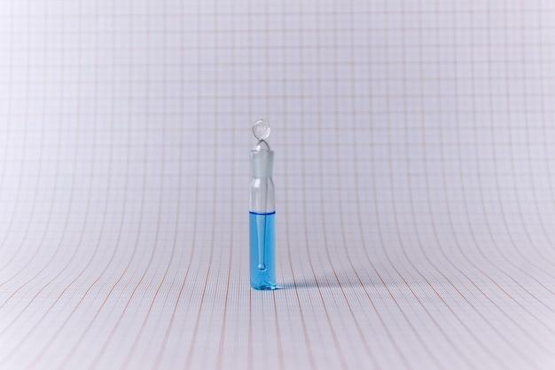Blaue flüssigkeit in glaswaren. kupfersulfatlösung in einem winzigen gefäß.