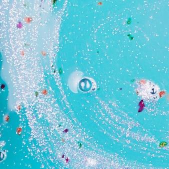 Blaue flüssigkeit mit klecksen und silberkrümeln