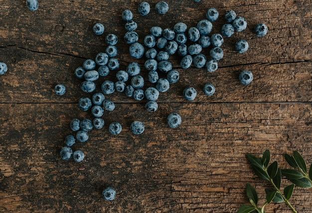 Blaue frische blaubeeren sind auf einem alten braunen hölzernen rissigen tisch verstreut.