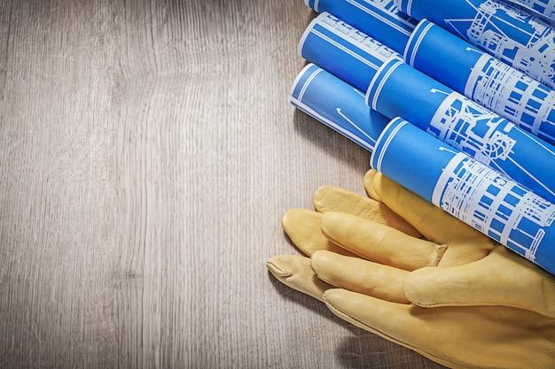 Blaue gerollte technische zeichnungen ledersicherheitshandschuhe auf holzbrettkonstruktionskonzept.