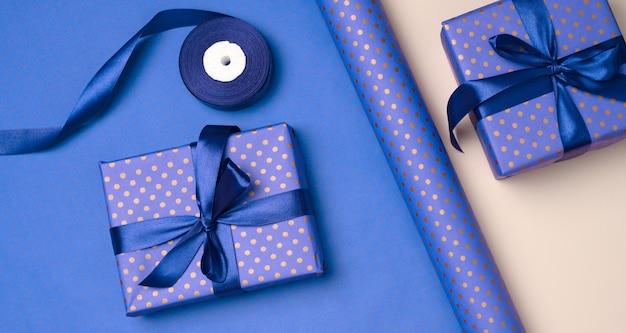 Blaue geschenkbox eingewickelt in seidenband auf blauem hintergrund, ansicht von oben
