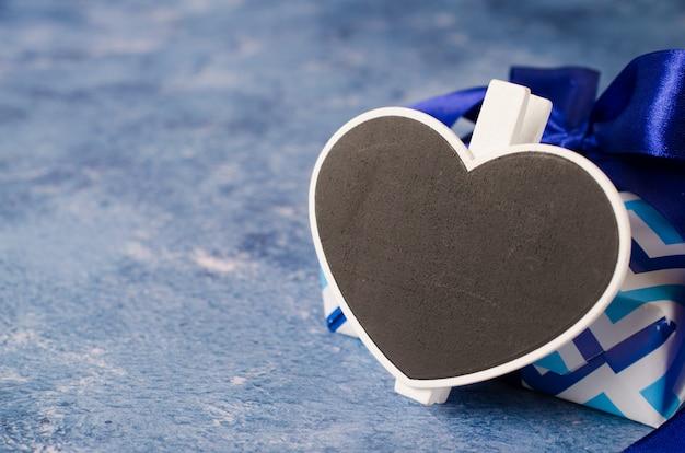 Blaue geschenkbox mit band. herzförmige tafel mit kopierraum.