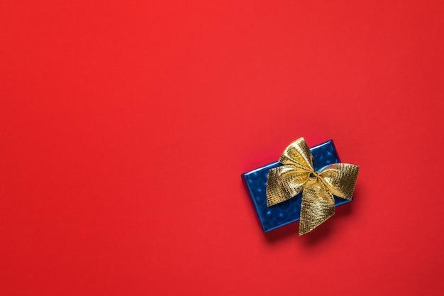 Blaue geschenkbox mit einer goldenen schleife auf einem roten hintergrund. ein überraschungsgeschenk.