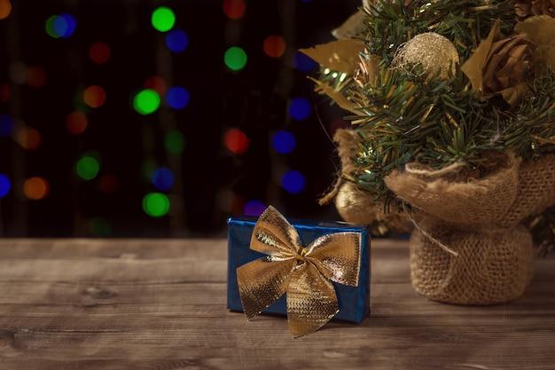 Blaue geschenkbox mit gelbem bogen unter einem weihnachtsbaum.