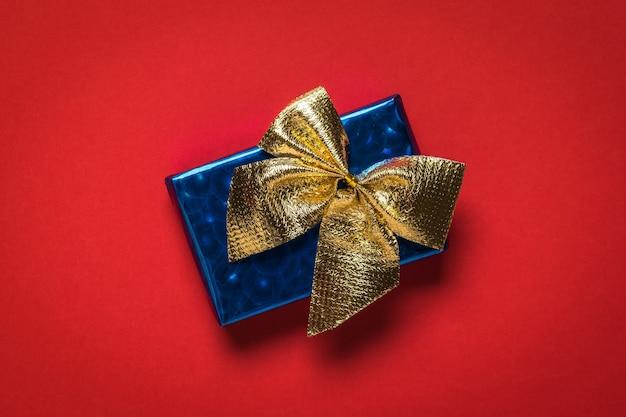 Blaue geschenkbox mit goldener schleife. ein überraschungsgeschenk.