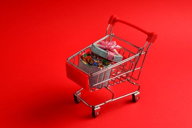 Blaue geschenkbox mit rosa schleife in einem einkaufswagen auf einer roten wand.
