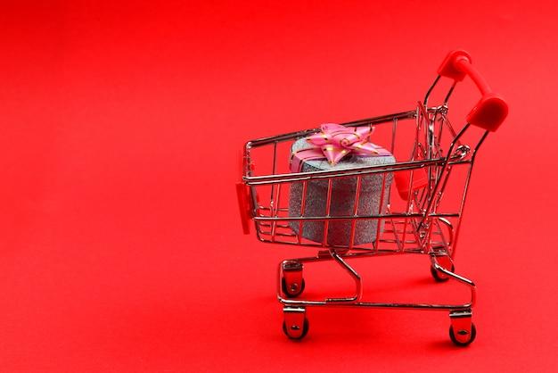 Blaue geschenkbox mit rosa schleife in einem einkaufswagen auf rotem hintergrund.