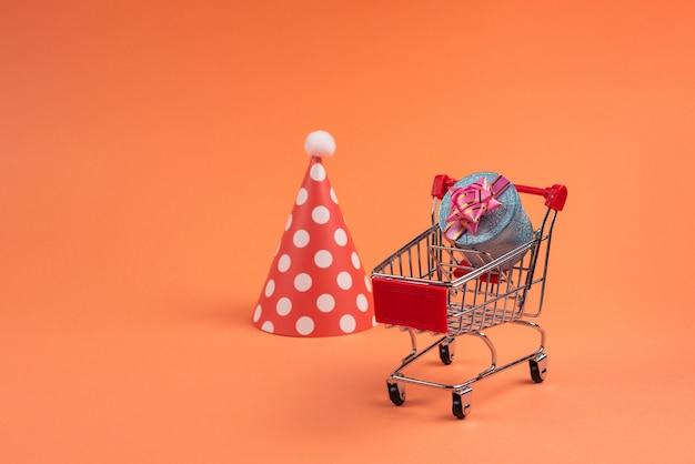 Blaue geschenkbox mit rosa schleife in einem einkaufswagen und geburtstagskappe auf einem roten