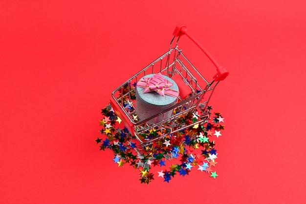 Blaue geschenkbox mit rosa schleife in einem einkaufswagen und konfetti auf einem roten hintergrund.