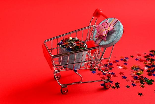 Blaue geschenkbox mit rosa schleife in einem einkaufswagen und konfetti auf rotem grund.