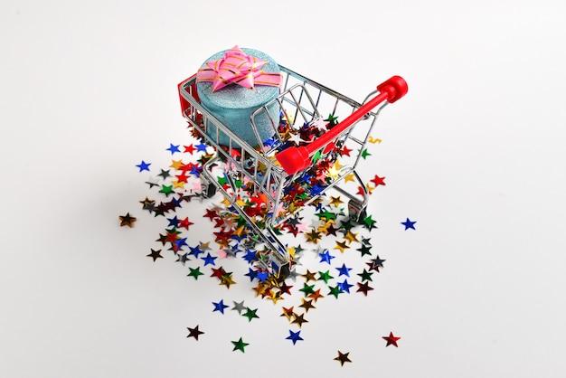 Blaue geschenkbox mit rosa schleife in einem einkaufswagen und konfetti auf weißem hintergrund.